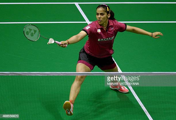 Saina Nehwal of India returns a shot against China's Li Xuerui during their women's singles semifinal match at the 2015 Malaysia Open Badminton...
