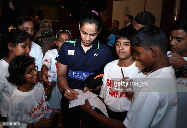 Saina Nehwal of India signs autographs for young fans after the draw and press conference ahead of the BWF Dubai World Superseries Finals at the...