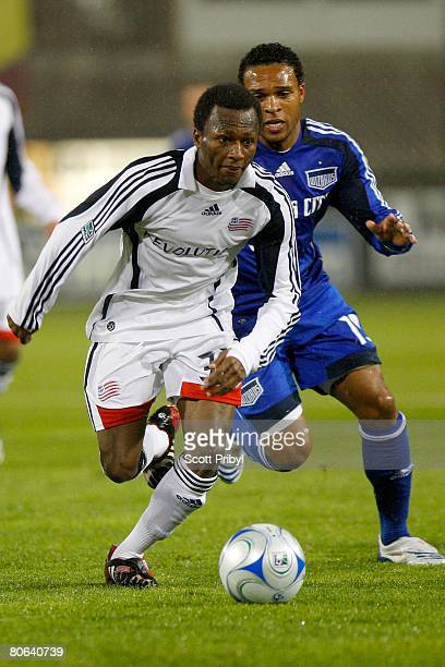 Sainey Nyassi of the New England Revolution dribbles away from Scott Sealy of the Kansas City Wizards during the game at Community America Ballpark...