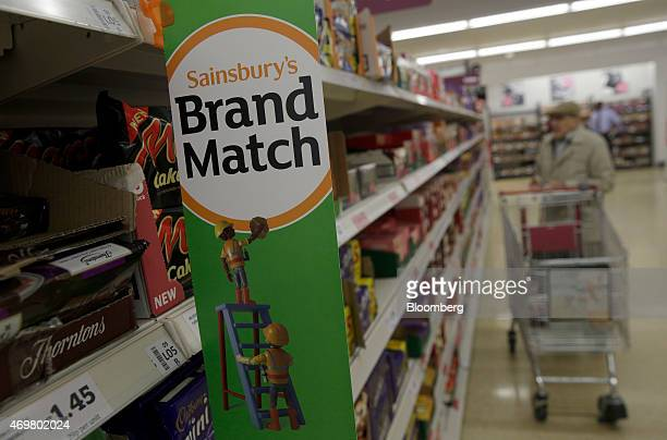 A Sainsbury's 'brand match' promotional poster hangs on a display shelf as a customer shops for confectionary inside a Sainsbury's supermarket store...