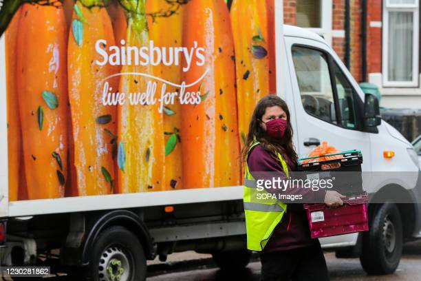 Sainsbury's deliveryman wearing a face mask carries crates as he delivers the shopping to a customer in London.