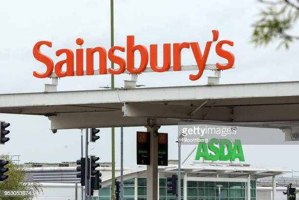 A Sainsbury's sign stands on top of a fuel station gantry in view of an Asda sign above the entrance to the supermarket in Watford UK on Monday April...