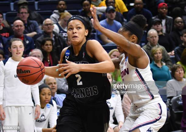 Saint Francis Red Flash Guard Caitlyn Kroll drives to the basket as UConn Huskies Guard Crystal Dangerfield defends during the game as the Saint...