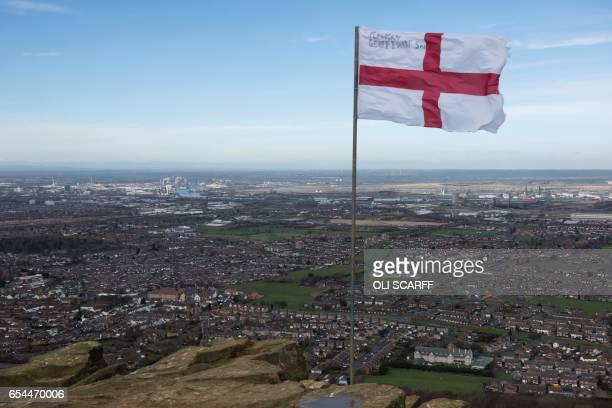 A Saint Geroge's Cross flag flies from the top of the outcrop Eston Nab overlooking Middlesbrough northern England on March 8 2017 / AFP PHOTO / OLI...