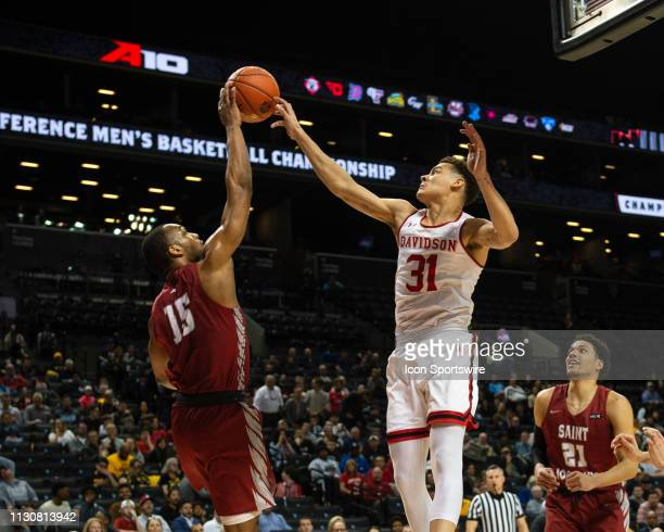 Saint Joseph's Hawks Guard Chris Clover and Davidson Wildcats Guard Kellan Grady compete for a rebound during the first half of the game between the...