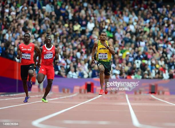 Saint Kitts Nevis' Antoine Adams Switzerland's Reto Schenkel and Jamaica's Warren Weir compete in the men's 200m heats at the athletics event during...