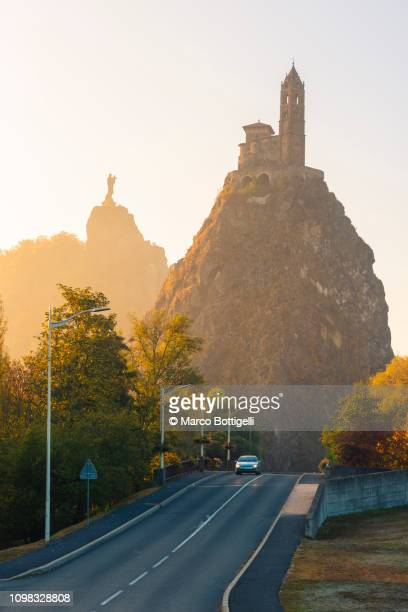 saint michel d'aiguilhe church and urban road in le puy en velay at sunrise, france - le puy stock pictures, royalty-free photos & images