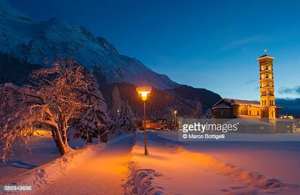 Saint Moritz church lights at dusk with pristine snow. Engadine, Switzerland, Europe