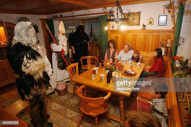 Saint Nicolas accompagnied by socalled Krampusse men traditionally dressed in skins speaks to children during his visit at a family on December 6...