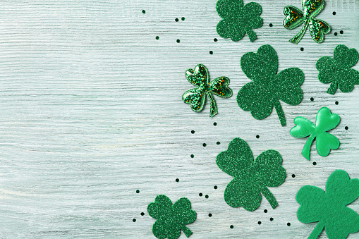 Saint Patricks Day background with green shamrock on white rustic board top view. 912065162