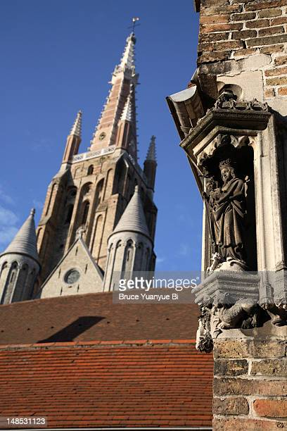 saint statue decorating corner of house with tower of church of our lady in background. - 西フランダース ストックフォトと画像