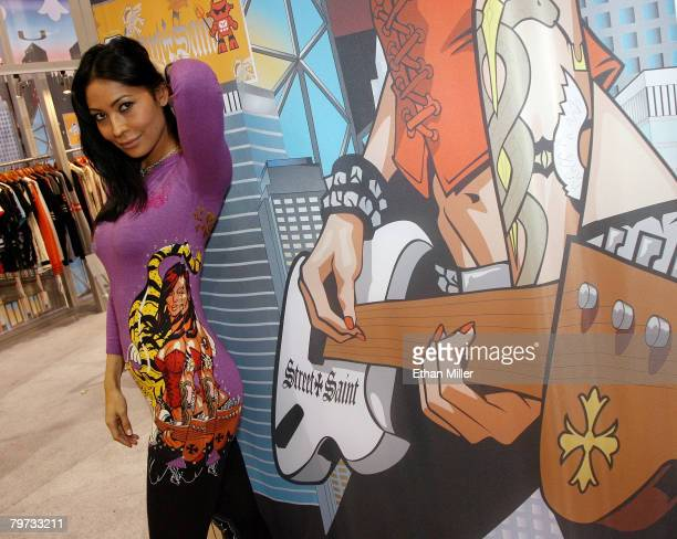 Saint Street Apparel spokesmodel Renee Esebag shows a new Evolution line piece featuring artwork of her at the company's booth at the MAGIC...