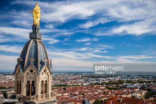 st. thomas kapelle luftaufnahme mit goldenen jungfrau maria statue von den dächern der basilika notre dame de fourviere mit lyon französischer stadt im hintergrund gesehen - byzanz stock-fotos und bilder