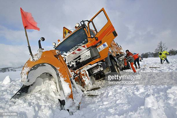 A snowplough sits in a ditch as it was clearing a road blocked by snowdrift near saintAgoulin central France 24 January 2007 Snow brought traffic...