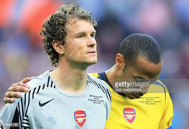 Arsenal's German goalkeeper Jens Lehmann is comforted by Arsenal's French forward and team captain Thierry Henry after he received a red card during...