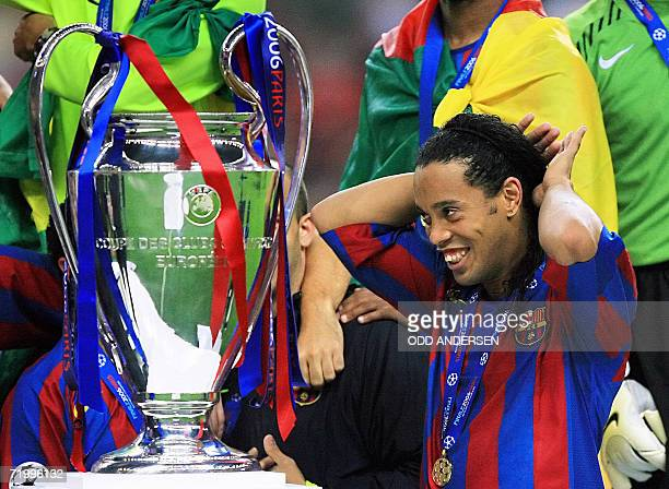 Barcelona's Brazilian midfielder Ronaldinho looks at the UEFA Champion's League trophy after winning the final football match against Arsenal 17 May...