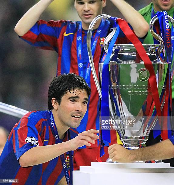 Barcelona's Portuguese midfielder Deco looks at the UEFA Champion's League trophy after winning the final football match againt Arsenal 17 May 2006...