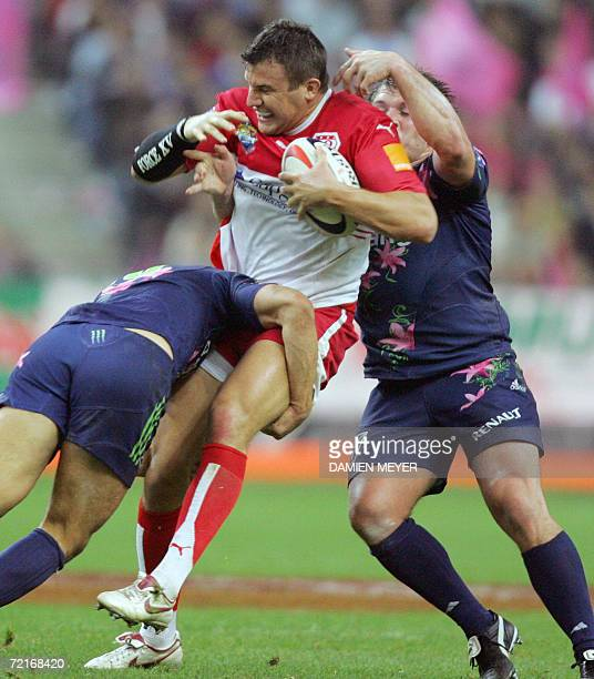 Biarritz's French fly-half Damien Traille is tackled by Stade Francais' French fly half David Skrela and Stade Francais' French prop Sylvain...