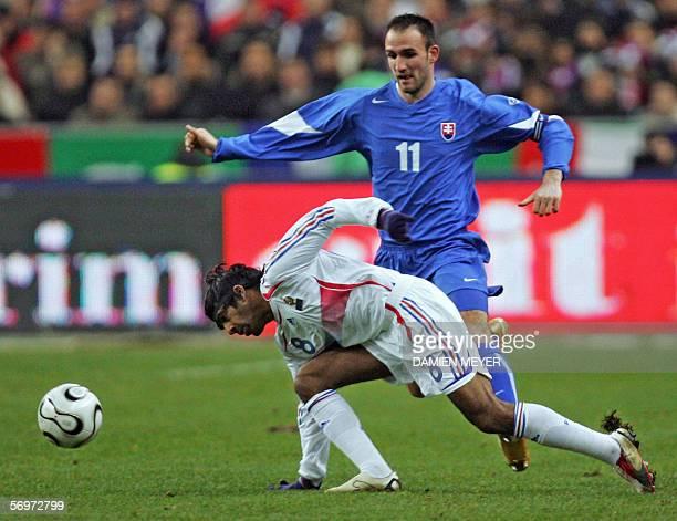 France's midfielder Vikash Dhorasoo vies with Slovakia's forward and captain Robert Vittek during the friendly football match France vs Slovakia as...