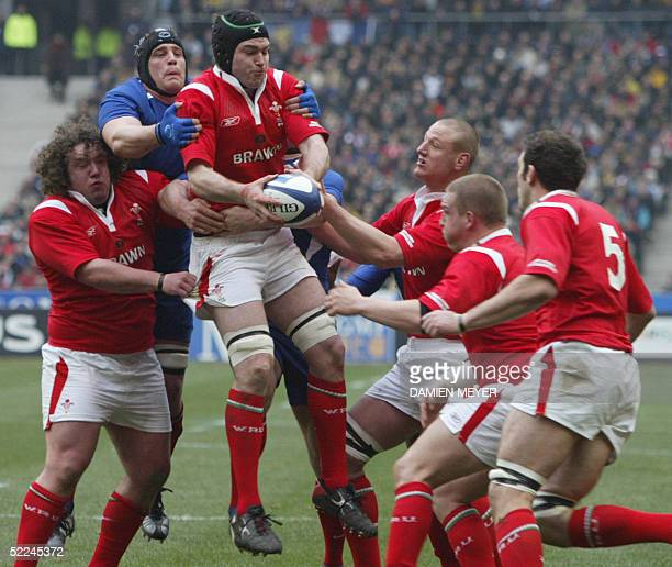 Welsh number eight Michael Owen catches the ball as French lock Jerome Thion tries to hold him despite defense of Wales players, prop Adam Jones ,...