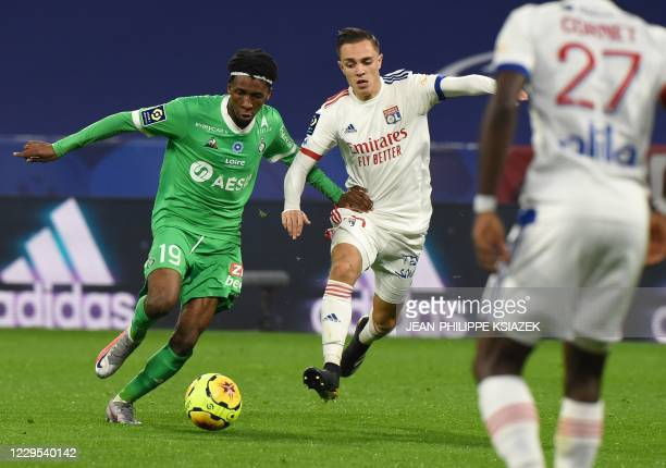 SaintEtienne's Camerounian midfielder Yvan Neyou fights for the ball withLyon's French midfielder Maxence Caqueret during the French L1 football...