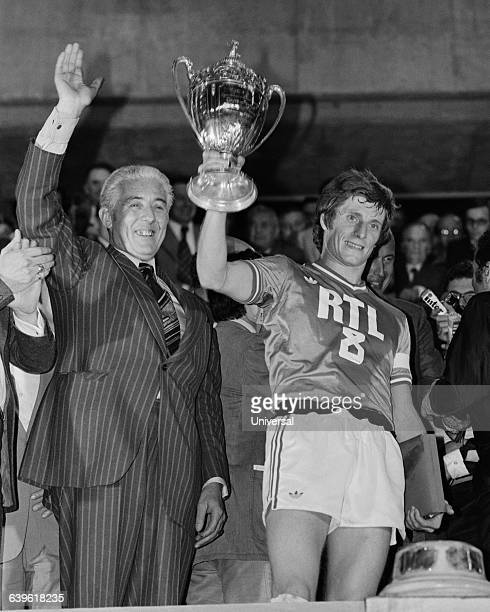 SaintEtienne's captain JeanMichel Larque holds the trophy next to ASSE President Roger Rocher following SaintEtienne's 20 victory over Lens in the...