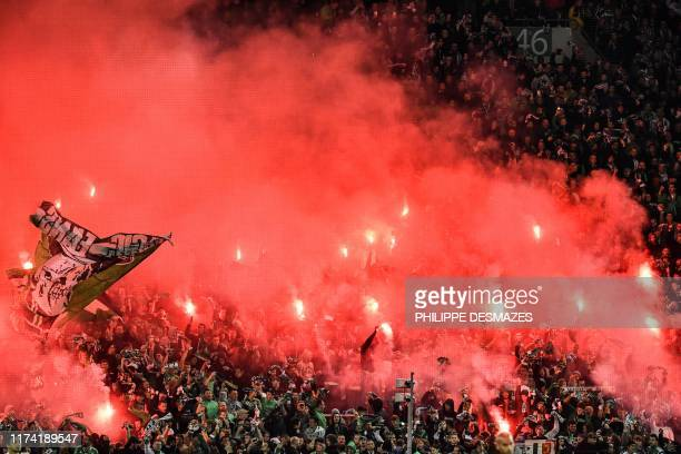 SaintEtienne's fans cheer and wave during the French L1 football match between AS SaintEtienne and Olympique Lyonnais at the Geoffroy Guichard...