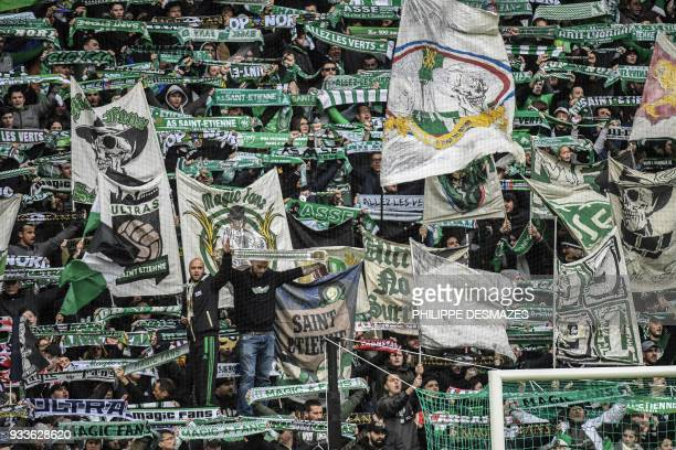 TOPSHOT SaintEtienne's fans wave during the French L1 football match between AS SaintEtienne and EA Guingamp on March 18 at the Geoffroy Guichard...