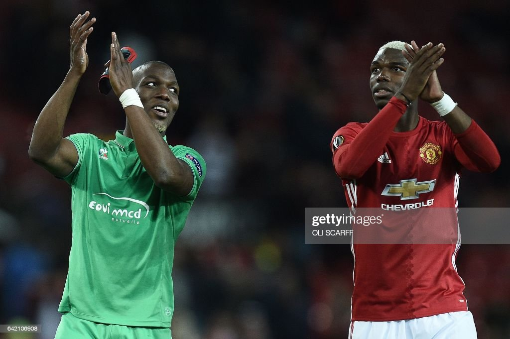 TOPSHOT - Saint-Etienne's French defender Florentin Pogba (L) and his bother Manchester United's French midfielder Paul Pogba applaud the fans following the UEFA Europa League Round of 32 first-leg football match between Manchester United and Saint-Etienne at Old Trafford stadium in Manchester, north-west England, on February 16, 2017. Manchester United won the match 3-0. / AFP / Oli SCARFF