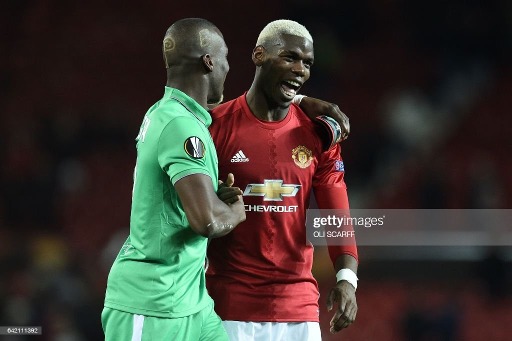 TOPSHOT - Saint-Etienne's French defender Florentin Pogba (L) and his bother Manchester United's French midfielder Paul Pogba react following the UEFA Europa League Round of 32 first-leg football match between Manchester United and Saint-Etienne at Old Trafford stadium in Manchester, north-west England, on February 16, 2017. Manchester United won the match 3-0. / AFP / Oli SCARFF