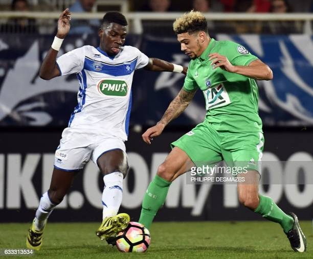 SaintEtienne's French defender Kevin Malcuit vies with Auxerre's French midfielder Brahim Konate during the French Cup football match between AJ...