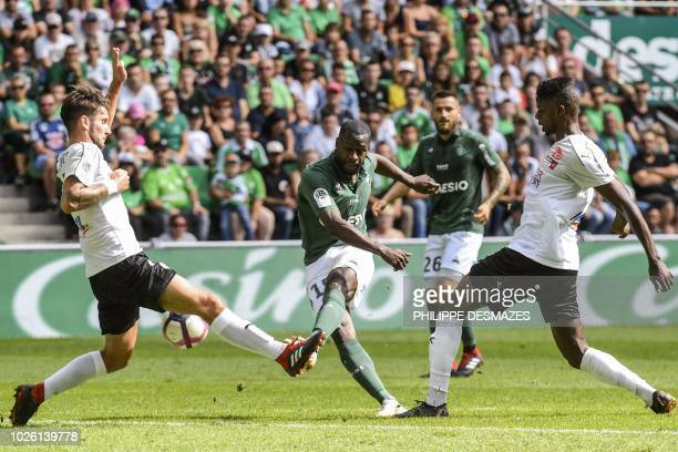 SaintEtienne's French defender Timothee Kolodziejczak shoots the ball despite of Amiens' African midfielder Bongani Zungu and Amiens' French defender...
