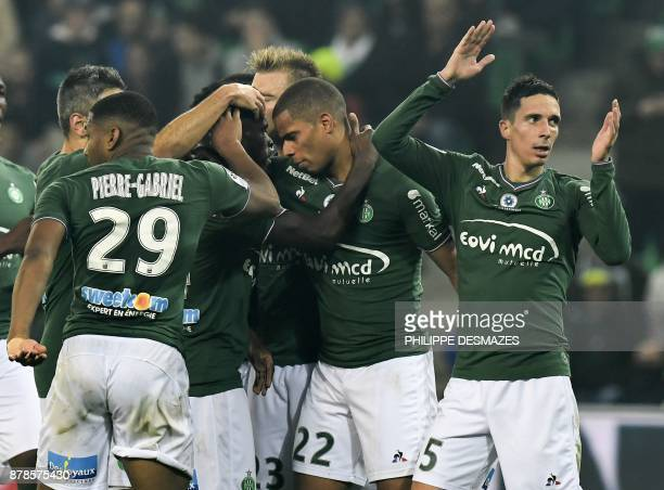 SaintEtienne's French forward Kevin MonnetPaquet is congratulated by teammates after scoring during the French L1 football match between AS...