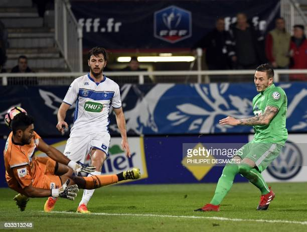 SaintEtienne's French forward Nolan Roux vies with Auxerre's French goalkeeper Zacharie Boucher during the French Cup football match between AJ...
