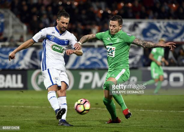 SaintEtienne's French forward Nolan Roux vies with Auxerre's French defender Mickael Tacalfred during the French Cup football match between AJ...