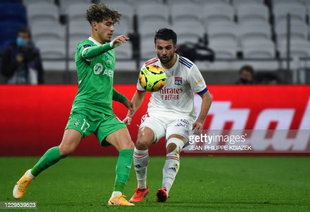 SaintEtienne's French midfielder Adil Aouchiche fights for the ball with Lyon's French defender Leo Dubois during the French L1 football match...
