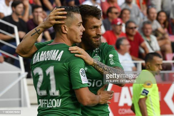 SaintEtienne's French midfielder Romain Hamouma is congratuled by teamate SaintEtienne's French defender Mathieu Debuchy after scoring a goal during...