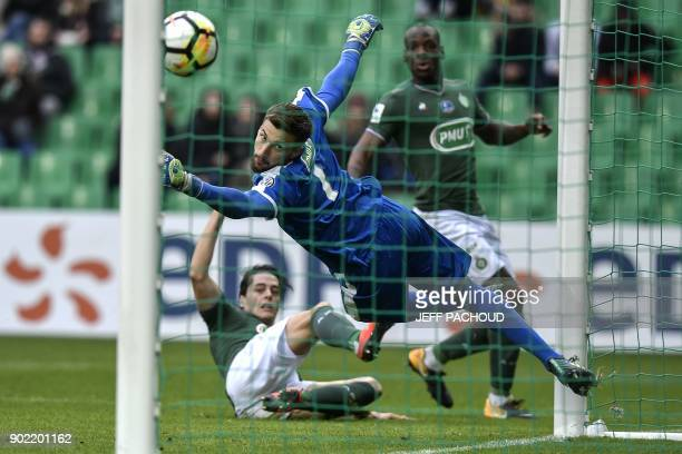 SaintEtienne's French midfielder Romain Hamouma tries to score as Nimes' French goalkeeper Baptiste Valette jumps to save the ball during the French...