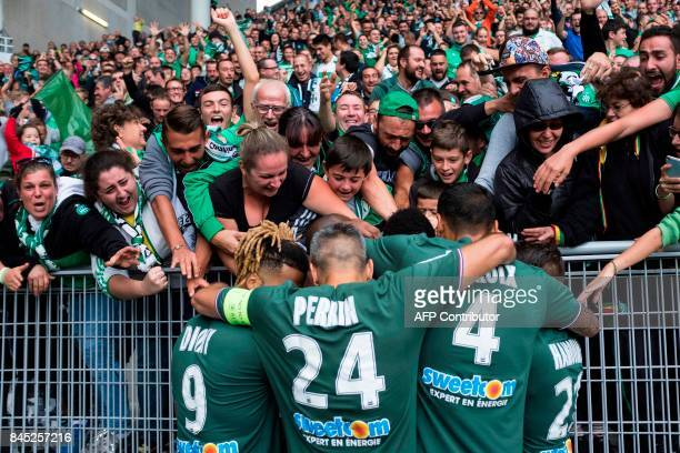 TOPSHOT SaintEtienne's players celebrate with fans after opening the scoring during the French L1 football match between SaintEtienne and Angers on...
