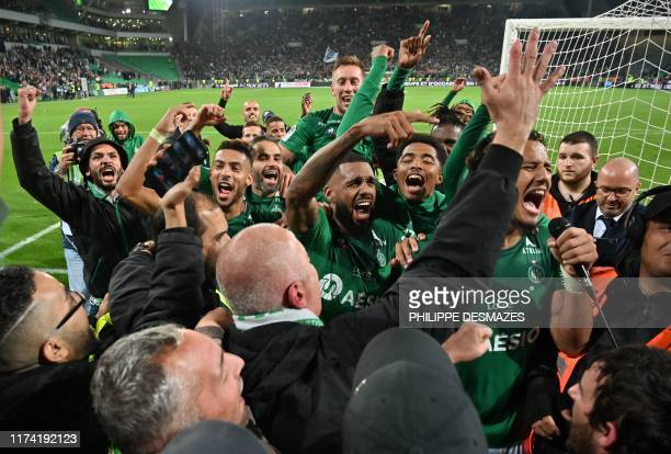 SaintEtienne's players celebrate with fans after winning the French L1 football match between AS SaintEtienne and Olympique Lyonnais at the Geoffroy...