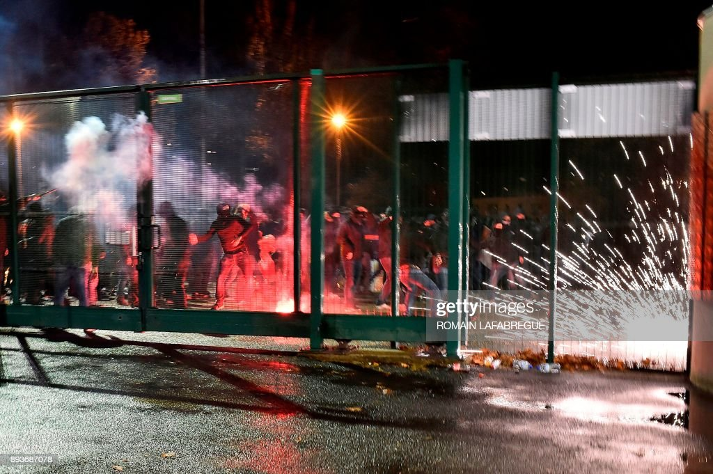 TOPSHOT - Saint-Etienne's supporters clash with police following the French L1 football match between Saint-Etienne (ASSE) and Monaco (ASM) on December 15, 2017, at the Geoffroy Guichard stadium in Saint-Etienne, central-eastern France. /