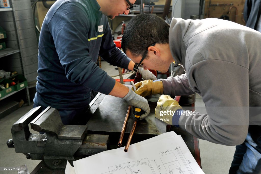'CFA', apprenticeship training center for the construction industry, training/work-experience contract . two young apprentices in the plumbing workshop.