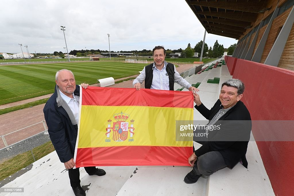 Saint-Martin-de-Re Mayor Patrice Dechelette (L), the president of the football club of Saint-Martin-de-Re, Michel Defontaine (C), and the president of the community of the Re Island, Lionel Quiellet (R), hold a Spanish national flag on May 25, 2016 in Saint-Martin-de-Ré, on the Re Island. The national football team of Spain will have its base camp on the island for the upcoming Euro 2016 European football championships. / AFP / XAVIER