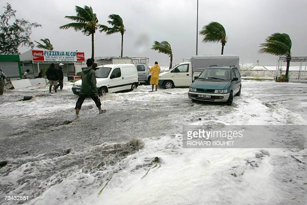 People walk on a flooded street near the seafront 27 February 2007 in SaintPaul de La Reunion as France's Indian Ocean island is under a cyclone...