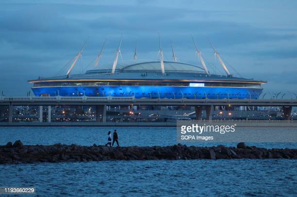 SaintPetersburg stadium as a couple walks by at 300 Years of StPetersburg Park during one of the warmest winters in history in Russia
