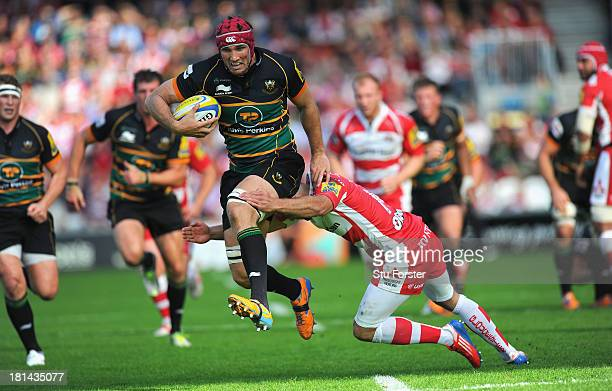 Saints player Christian Day runs through the tackle of Gloucester wing Charlie Sharples during the Aviva Premiership match between Gloucester and...