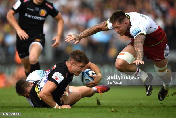 Saints player Dan Biggar tackles Ollie Devoto as Teimana Harrison joins in during the Gallagher Premiership Rugby Semi Final match between Exeter...
