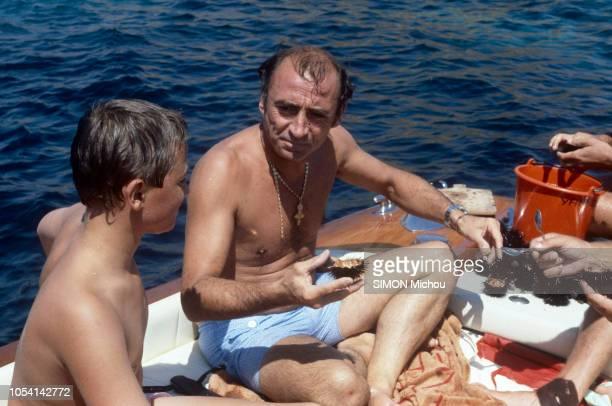 SaintTropez France 8 août 1985 L'acteur Claude BRASSEUR en vacances ouvrant des oursins sur son bateau avec son fils Alexandre