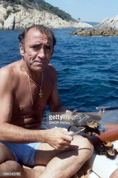 SaintTropez France 8 août 1985 L'acteur Claude BRASSEUR en vacances avec son fils Alexandre Ici en maillot de bain ouvrant des oursins à bord de son...