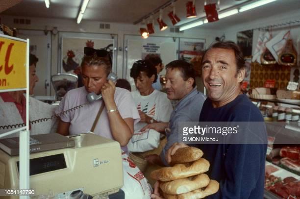 SaintTropez France 8 août 1985 L'acteur Claude BRASSEUR en vacances avec son fils Alexandre Ici souriant et achetant du pain dans un commerce